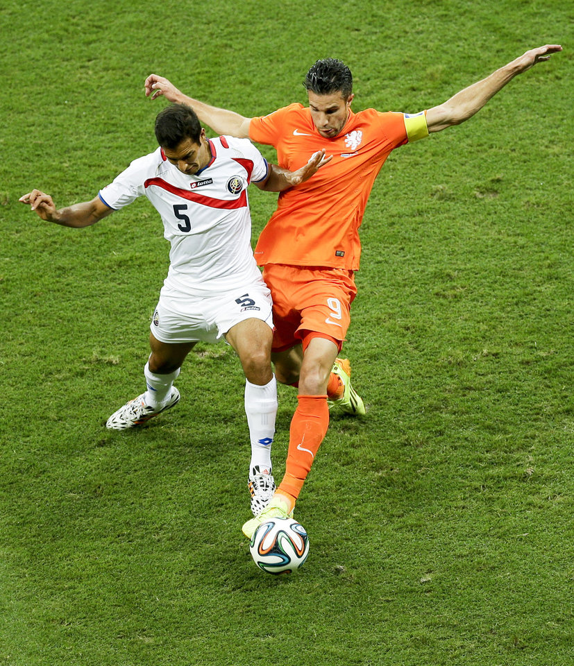 Photo - Costa Rica's Celso Borges, left, and Netherlands' Robin van Persie go for the ball during the World Cup quarterfinal soccer match between the Netherlands and Costa Rica at the Arena Fonte Nova in Salvador, Brazil, Saturday, July 5, 2014. (AP Photo/Themba Hadebe)