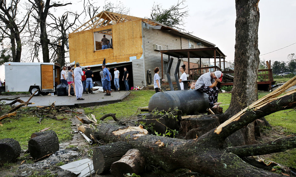 Photo - Family and neighbors help the owner of this damaged home on US 177 north of I-40. A tornado caused extensive damage along I-40 at the junction with  US 177 on the west side of Shawnee Sunday evening,  May 19,  2013.  Photo  by Jim Beckel, The Oklahoman.
