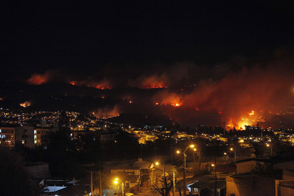 Photo - An out of control forest fire rages towards urban areas in the city of Valparaiso, Chile, Saturday, April 12, 2014. Authorities say the forest fire has destroyed at least 150 homes and is forcing evacuations. ( AP Photo/ Luis Hidalgo)