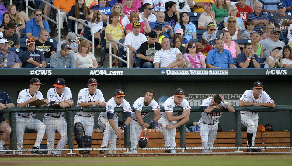 Photo - Virginia players watch from the bench in the third inning of the opening game of the best-of-three NCAA baseball College World Series finals against Vanderbilt in Omaha, Neb., Monday, June 23, 2014. (AP Photo/Ted Kirk)