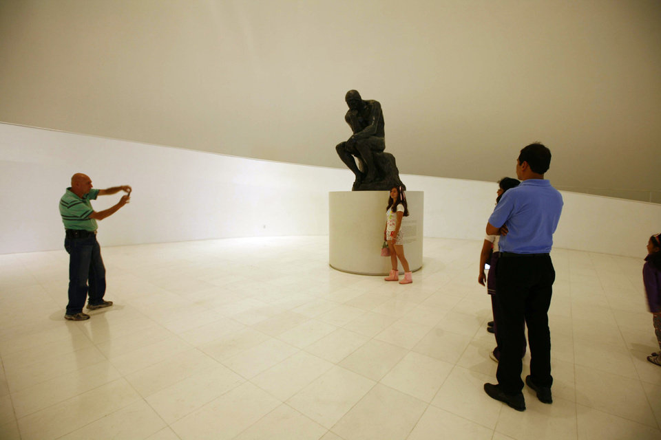 Photo -   People take photos next to an Auguste Rodin sculpture at the Soumaya Museum in Mexico City, Monday, Nov. 19, 2012. On the northern edge of Mexico City's Polanco neighborhood, home to gleaming office towers, high-end restaurants and luxury boutiques, billionaire Carlos Slim has erected the mirrored, mushroom-shaped Soumaya museum, home to six floors of Impressionists, Old Masters, Mexican muralists, anonymous Mesoamerican craftsmen and hundreds of other works. The museum is open daily, from 10:30 a.m. to 6:30 p.m. and admission is free. (AP Photo/Marco Ugarte)