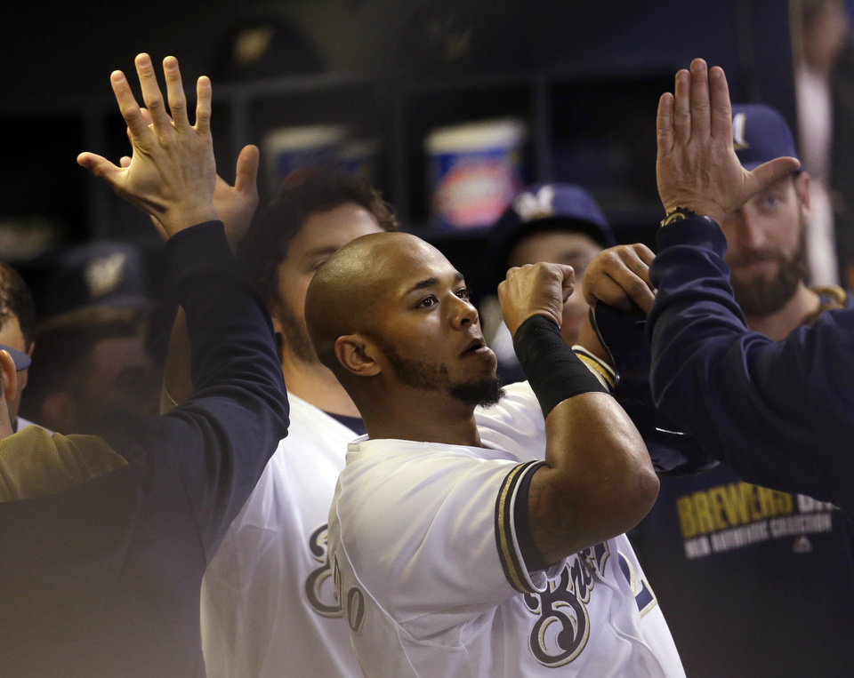 Photo - Milwaukee Brewers' Martin Maldonado is congratulated in the dugout after hitting a two-run home run during the second inning of a baseball game against the Arizona Diamondbacks Monday, May 5, 2014, in Milwaukee. (AP Photo/Morry Gash)