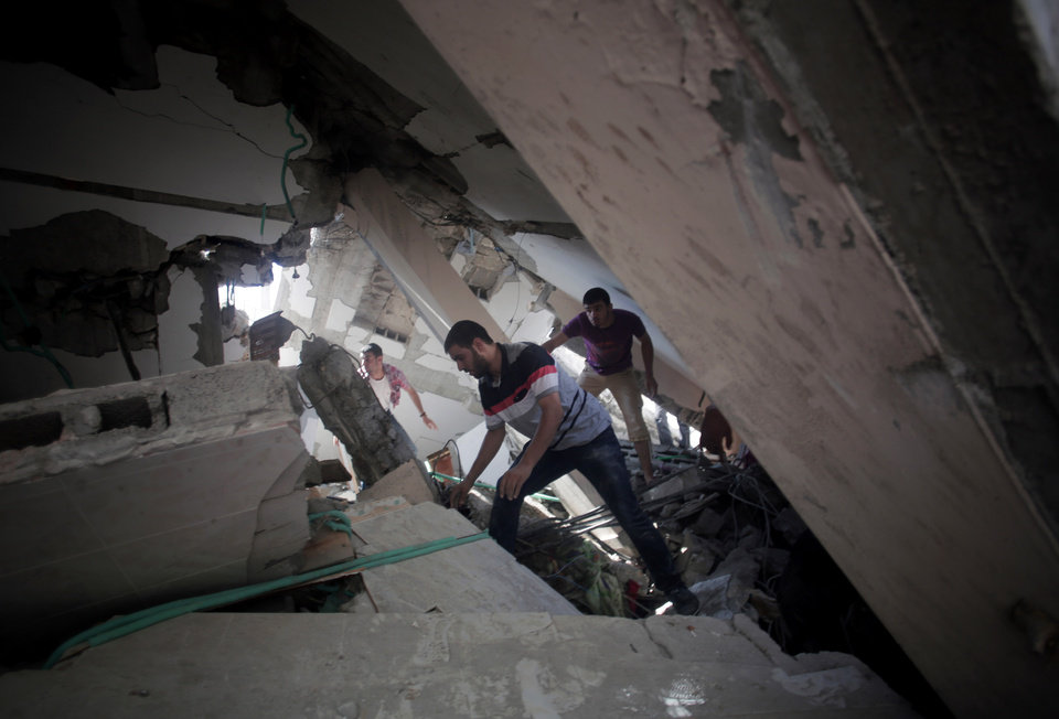 Photo - Palestinians search for survivors under the rubble of a house was destroyed by an Israeli missile strike, in Gaza City, Monday, July 21, 2014. On Sunday, the first major ground battle in two weeks of Israel-Hamas fighting exacted a steep price, killing scores of Palestinians and over a dozen Israeli soldiers and forcing thousands of terrified Palestinian civilians to flee their devastated Shijaiyah neighborhood, which Israel says is a major source for rocket fire against its civilians. (AP Photo/Khalil Hamra)