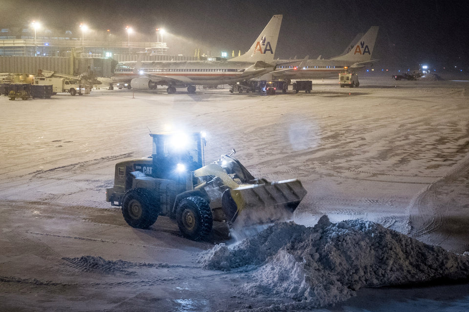 Photo - Crews work to remove the snow from the tarmac at Reagan National Airport in Washington Tuesday evening, Jan. 21, 2014, after winter storm socked in the Mid-Atlantic region. (AP Photo/J. David Ake)