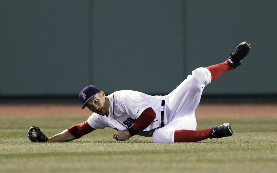 Photo - Boston Red Sox center fielder Grady Sizemore rolls as he makes the catch on a sacrifice fly by Texas Ranger Mitch Moreland, which scored Adrian Beltre, during the fourth inning of a MLB baseball game at Fenway Park, Monday, April 7, 2014, in Boston.(AP Photo/Charles Krupa)