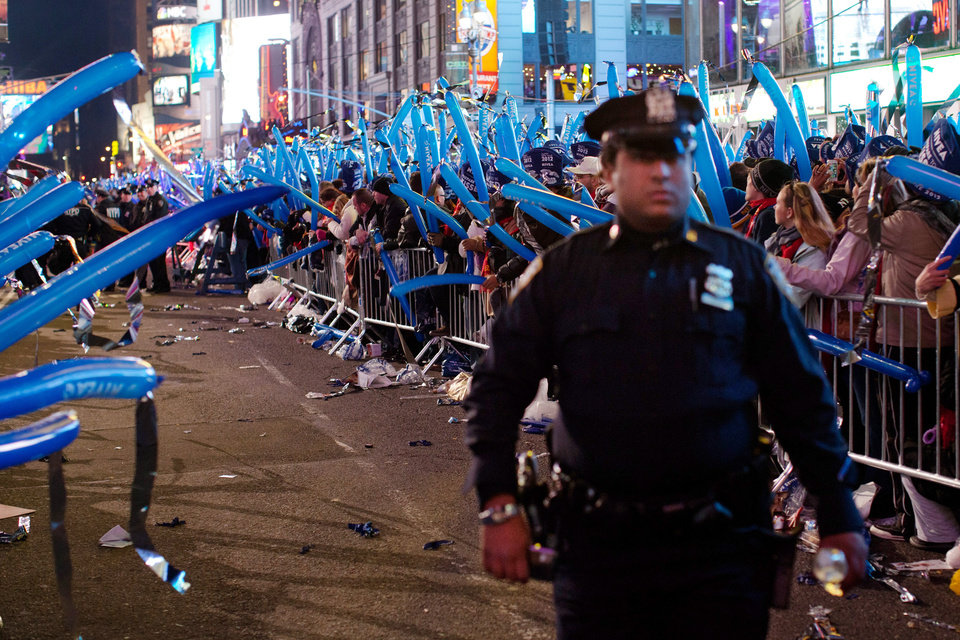 "FILE - In this Dec. 31, 2011 file photo, a police officer walks through a frozen zone in New York City's Times Square as revelers wave balloons in anticipation of midnight. The New York City police use an array of security measures for the event that turns the ""Crossroads of the World"" into a massive street party in the heart of Manhattan. (AP Photo/John Minchillo, File)"
