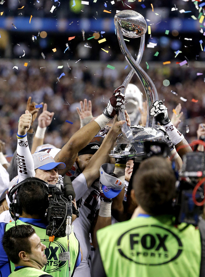 Photo - Texas A&M 's Johnny Manziel celebrates with the trophy after the Cotton Bowl college football game between the University of Oklahoma (OU)and Texas A&M University at Cowboys Stadium in Arlington, Texas, Friday, Jan. 4, 2013. Oklahoma lost 41-13. Photo by Bryan Terry, The Oklahoman