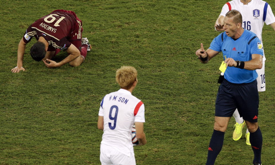 Photo - Referee Nestor Pitana, from Argentina, right, books South Korea's Son Heung-min (9) after he fouled Russia's Alexander Samedov (19) during the group H World Cup soccer match between Russia and South Korea at the Arena Pantanal in Cuiaba, Brazil, Tuesday, June 17, 2014. (AP Photo/Thanassis Stavrakis)