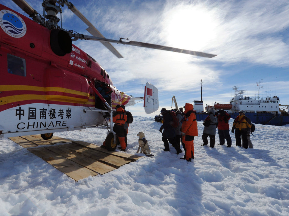 Photo - In this photo provided China's official Xinhnua News Agency, passengers from the trapped Russian vessel MV Akademik Shokalskiy, seen at right, prepare to board the Chinese helicopter Xueying 12 in the Antarctic Thursday, Jan. 2, 2014. A helicopter rescued all 52 passengers from the research ship that has been trapped in Antarctic ice, 1,500 nautical miles south of Hobart, Australia, since Christmas Eve after weather conditions finally cleared enough for the operation Thursday. (AP Photo/Xinhua, Zhang Jiansong) NO SALES