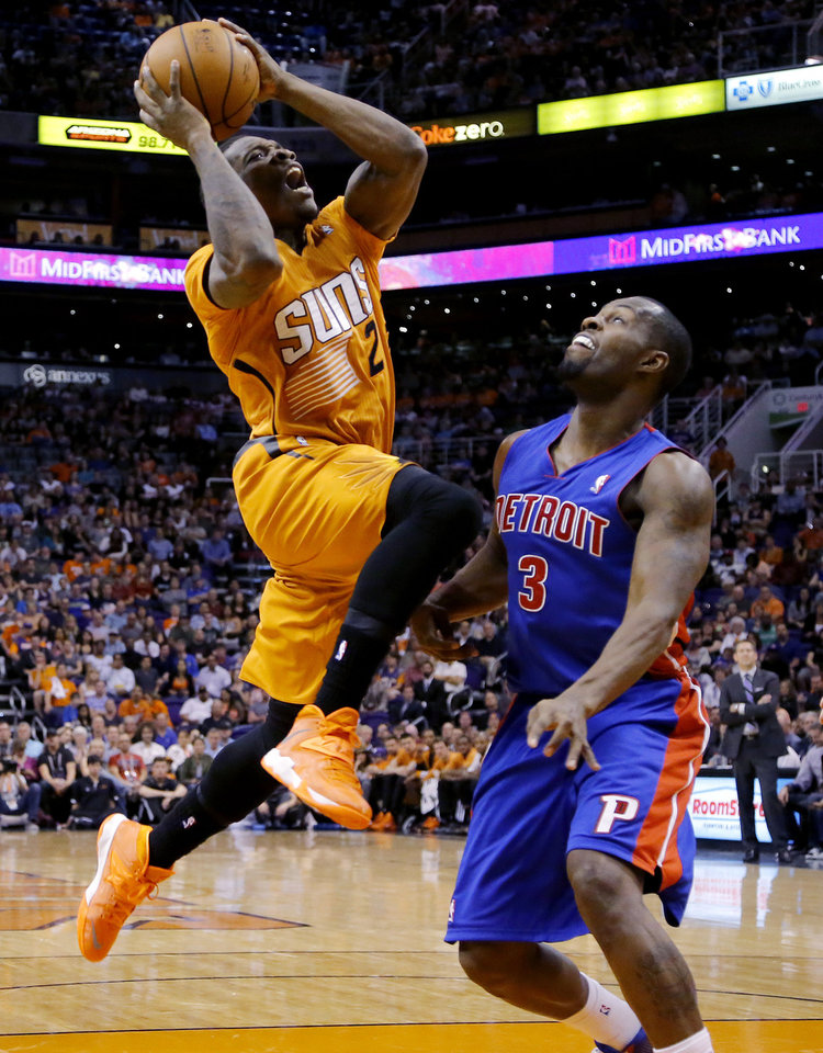 Photo - Phoenix Suns' Eric Bledsoe (2) goes in for a shot as Detroit Pistons' Rodney Stuckey defends during the second half of an NBA basketball game, Friday, March 21, 2014, in Phoenix. The Suns won 98-92. (AP Photo/Matt York)