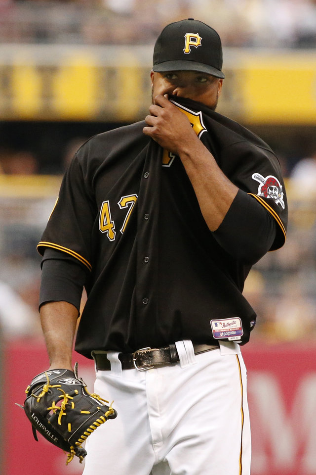 Photo - Pittsburgh Pirates starting pitcher Francisco Liriano wipes his face after walking Colorado Rockies' Troy Tulowitzki during the first inning of a baseball game against the Colorado Rockies in Pittsburgh Friday, July 18, 2014. (AP Photo/Gene J. Puskar)