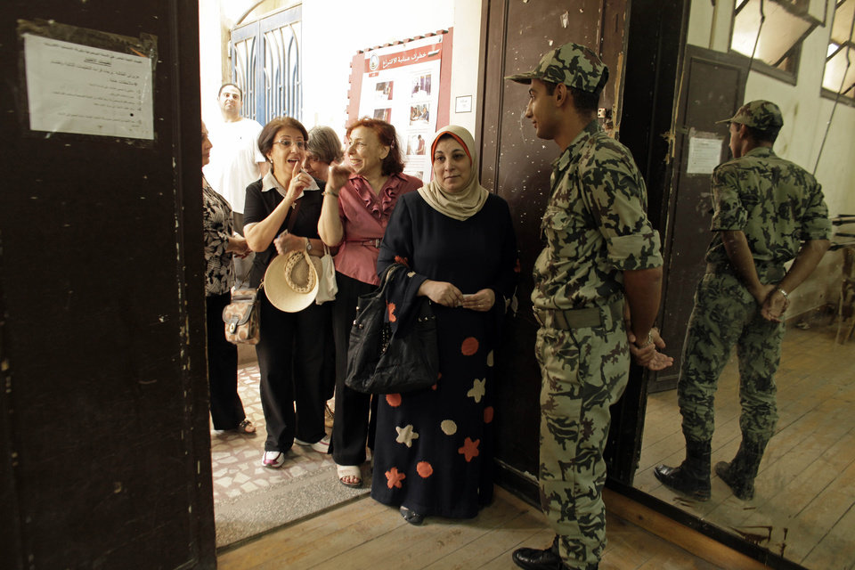 Photo -   An Egyptian Army soldier stands guard inside a polling station as women wait to cast their votes in the country's presidential election on Wednesday, May 23, 2012 in the Zamalek neighborhood of Cairo, Egypt. Determined to end decades of authoritarian rule, millions of Egyptians on Wednesday waited patiently in long lines outside polling stations across the nation to freely chose their first president since last year's ouster of longtime ruler and close U.S. ally Hosni Mubarak. (AP Photo/Maya Alleruzzo)