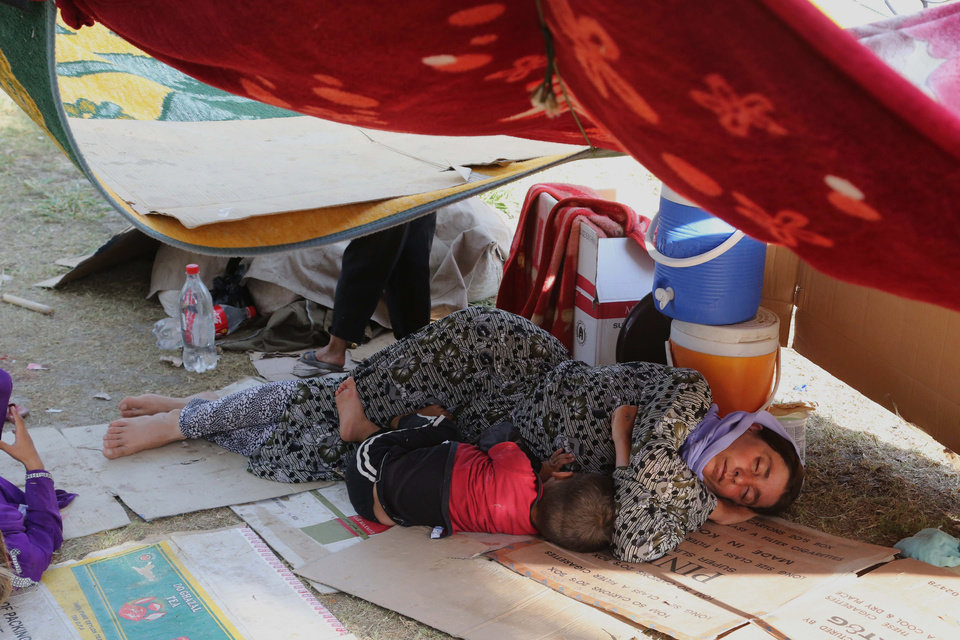 Photo - An Iraqi woman and her son from the Yazidi community sleep at a park near the Turkey-Iraq border at the Ibrahim al-Khalil crossing, as they try to cross to Turkey, in Zakho, 300 miles (475 kilometers) northwest of Baghdad, Iraq, Friday, Aug. 15, 2014. The U.N. this week declared the situation in Iraq a