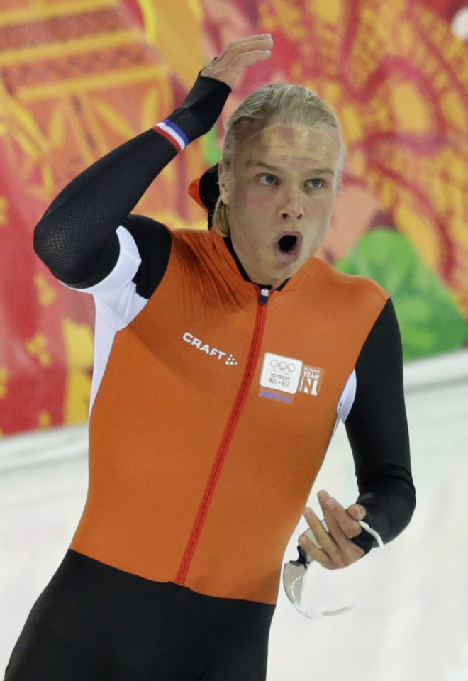 Photo - Silver medallist Koen Verweij of the Netherlands raises his hand when the race was declared a tie with gold medallist Poland's Zbigniew Brodka  in the men's 1,500-meter speedskating race at the Adler Arena Skating Center during the 2014 Winter Olympics in Sochi, Russia, Saturday, Feb. 15, 2014. Verweij later was later declared silver, losing by three thousandth of a second. (AP Photo/Matt Dunham)
