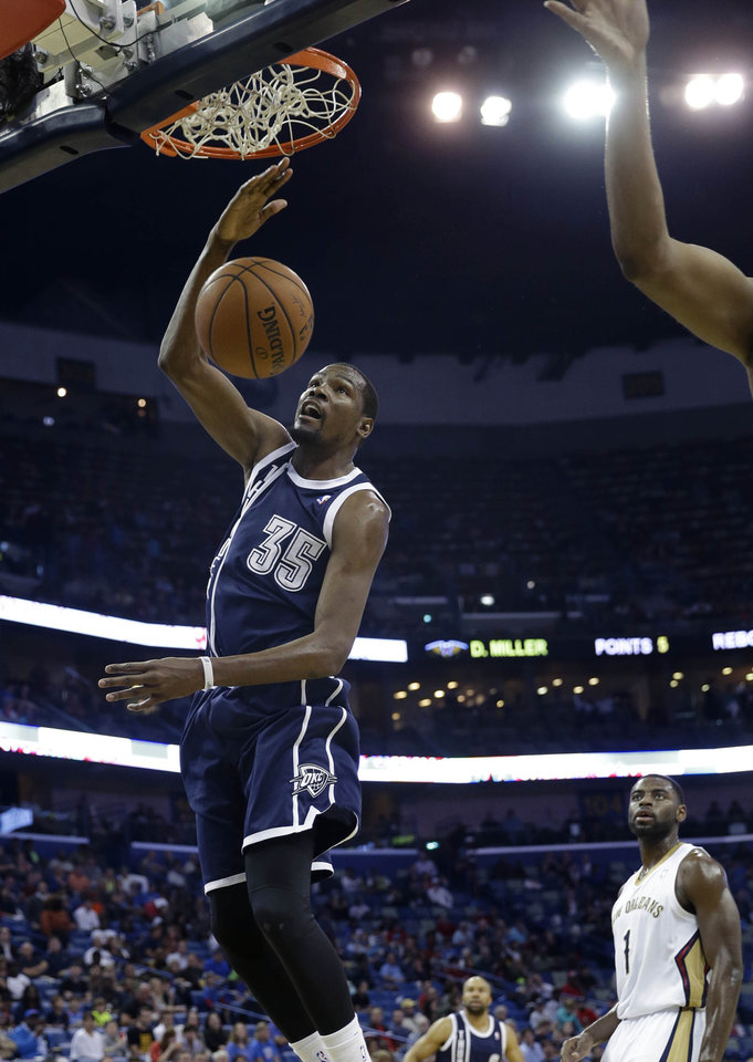 Photo - Thunder forward Kevin Durant, left, dunks as Pelicans forward Tyreke Evans watches in the first half Monday in New Orleans.                    AP Photo
