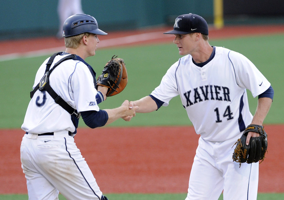 Photo - Xavier's closer Sean Campbell celebrates with catcher Daniel Rizzie, left, after defeating St. John's, 8-2, in an NCAA college baseball game in the Big East tournament Friday, May 23, 2014, in New York. (AP Photo/Bill Kostroun)