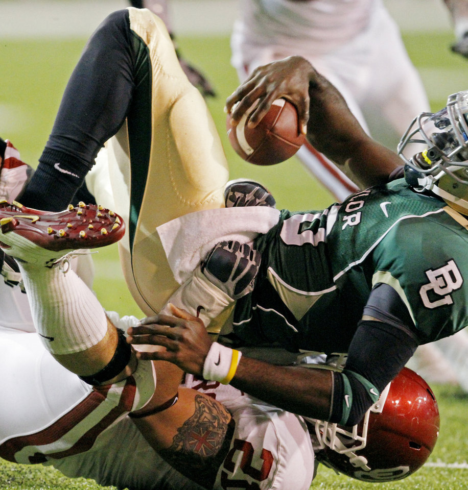 Photo - Tom Wort (21) brings down Baylor quarterback Robert Griffin III during the first half of the college football game between the University of Oklahoma Sooners (OU) and the Baylor Bears (BU) at Floyd Casey Stadium on Saturday, November 20, 2010, in Waco, Texas.   Photo by Steve Sisney, The Oklahoman