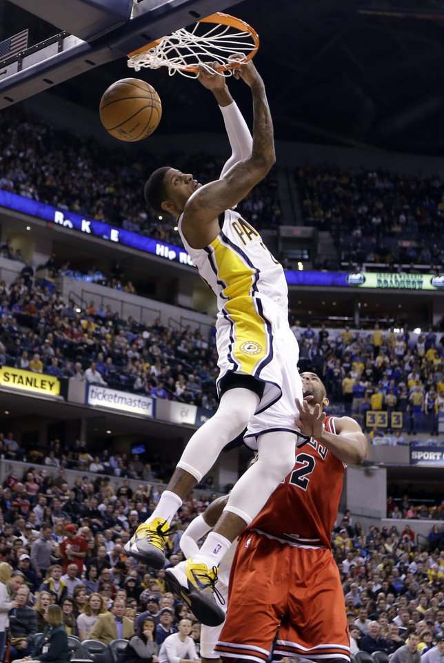 Photo - Indiana Pacers forward Paul George gets a reverse dunk over Chicago Bulls forward Taj Gibson in the second half of an NBA basketball game in Indianapolis, Monday, Feb. 4, 2013. The Pacers defeated the Bulls 111-101. (AP Photo/Michael Conroy)