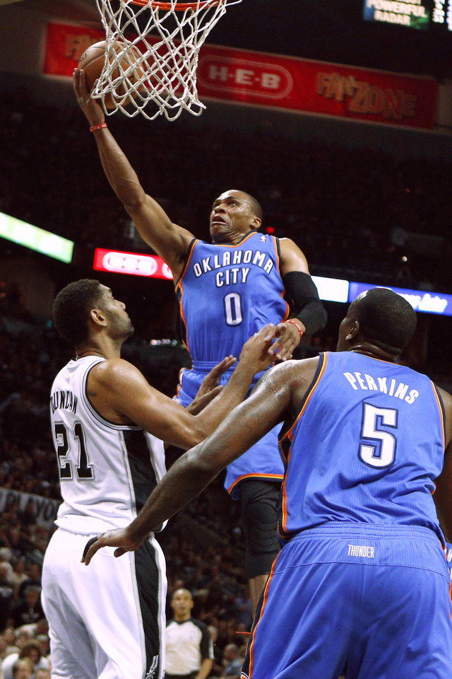 Photo - Oklahoma City's Russell Westbrook (0) goes to the basket in front of San Antonio's Tim Duncan (21) during Game 1 of the Western Conference Finals in the NBA playoffs between the Oklahoma City Thunder and the San Antonio Spurs at the AT&T Center in San Antonio, Monday, May 19, 2014. Photo by Sarah Phipps, The Oklahoman