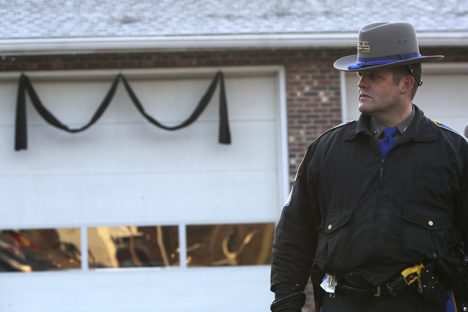 Photo - Bunting hangs on the Sandy Hook fire house as a Connecticut State Trooper stands guard outside, Saturday, Dec. 15, 2012 in Sandy Hook village of Newtown, Conn.   The massacre of 26 children and adults at Sandy Hook Elementary school elicited horror and soul-searching around the world even as it raised more basic questions about why the gunman, 20-year-old Adam Lanza, would have been driven to such a crime and how he chose his victims.  (AP Photo/Mary Altaffer)