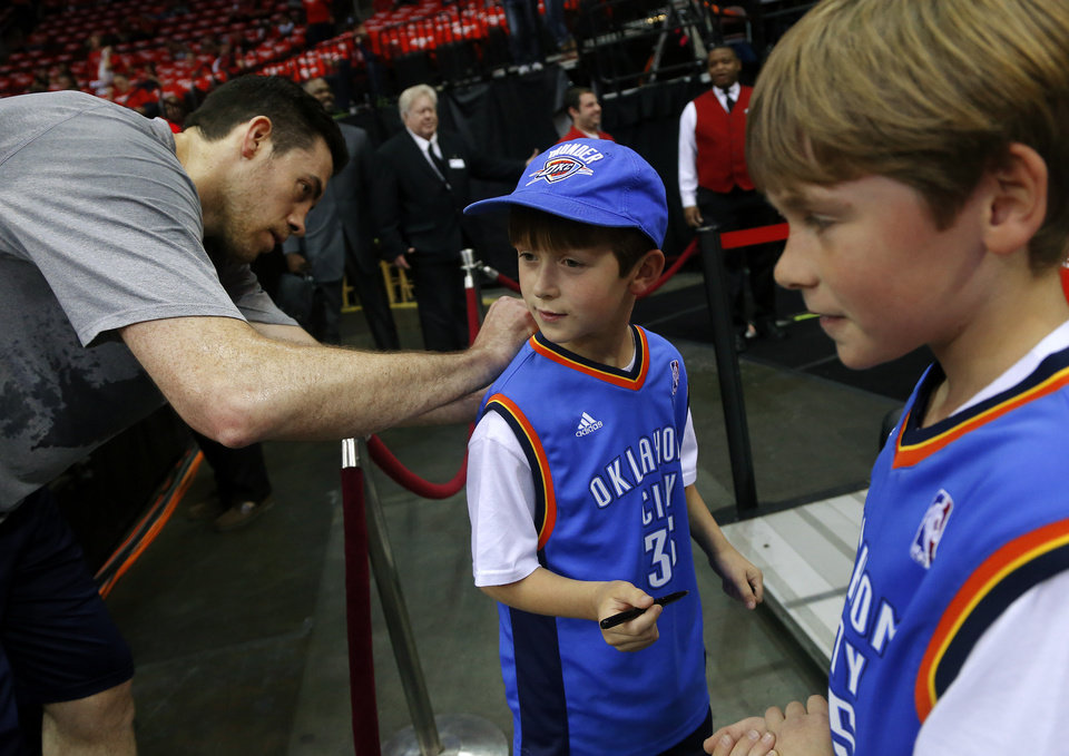Photo - Nelson Mathis, 8, of Oklahoma City has his jersey signed by Oklahoma City's Nick Collison as his brother William Mathis, 10, at right, watches before Game 6 in the first round of the NBA playoffs between the Oklahoma City Thunder and the Houston Rockets at the Toyota Center in Houston, Texas, Friday, May 3, 2013. Photo by Bryan Terry, The Oklahoman