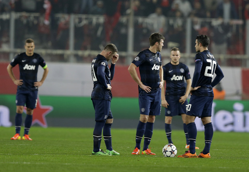 Photo - Manchester United's players react after Olympiakos' Alejandro Dominguez scored the opening goal of his team during their Champions League, round of 16, first leg soccer match at Georgios Karaiskakis stadium, in Piraeus port, near Athens, on Tuesday, Feb. 25, 2014. (AP Photo/Thanassis Stavrakis)