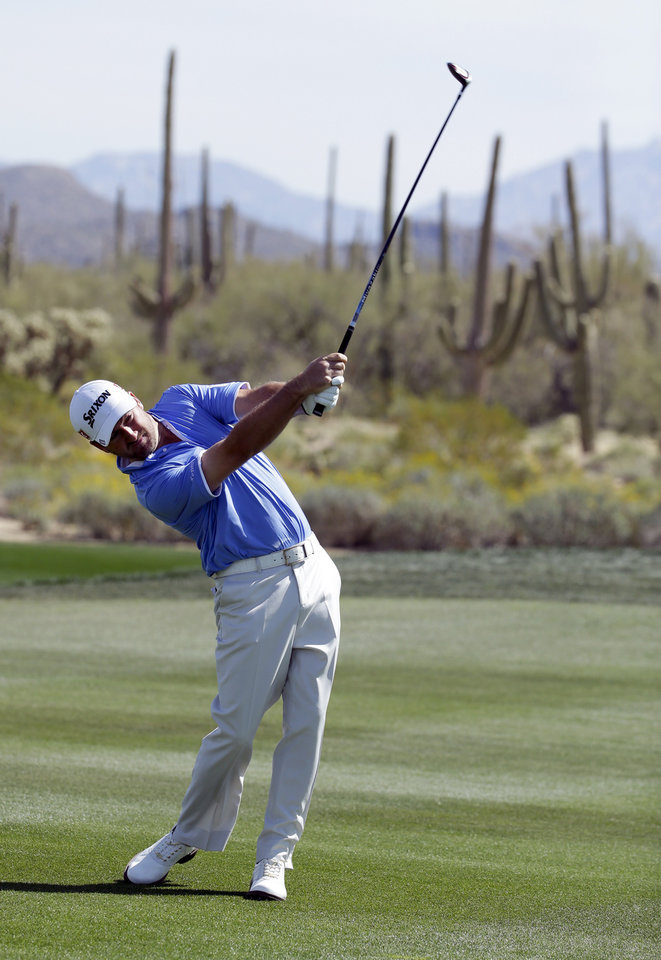 Photo - Graeme McDowell, of Northern Ireland, hits from the fairway on the second hole in his match against Victor Dubuisson, of France, during the fourth round of the Match Play Championship golf tournament on Saturday, Feb. 22, 2014, in Marana, Ariz. (AP Photo/Ted S. Warren)