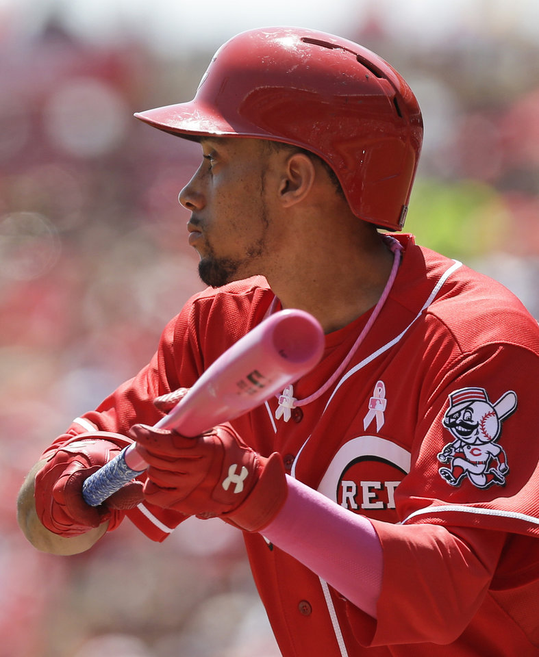 Photo - Cincinnati Reds' Billy Hamilton squares to bun against Colorado Rockies starting pitcher Juan Nicasio in the first inning of a baseball game, Sunday, May 11, 2014, in Cincinnati. Hamilton was using a pink bat for Mother's Day. Hamilton bunted for a single in the at bat. (AP Photo/Al Behrman)