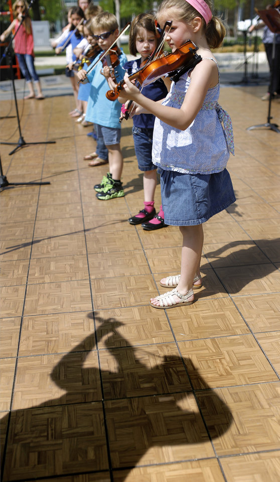 Photo -  At right:  Music teacher Sarah Grote's shadow can be seen as she leads Metro Fiddle Club students in a performance Wednesday on the Great Lawn Stage at the Festival of the Arts.   Photos by Jim Beckel, The Oklahoman   Jim Beckel