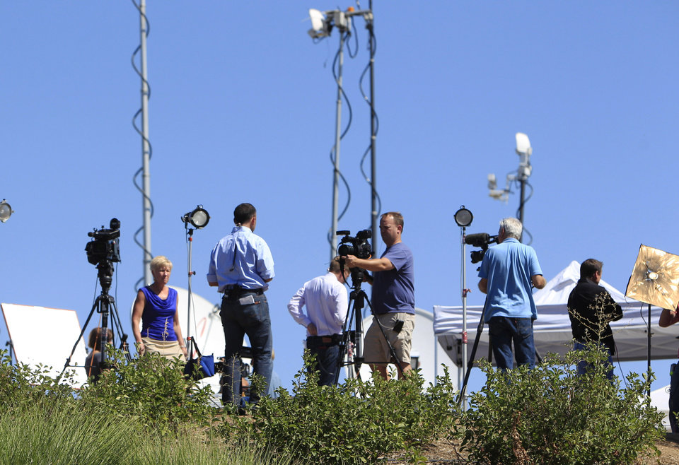 Photo - Television reporters line up on hillside near the Century 16 movie theater east of the Aurora Mall in Aurora, Colo. on Friday, July 20, 2012. A gunman in a gas mask barged into the crowded Denver-area theater during a midnight showing of the Batman movie on Friday, hurled a gas canister and then opened fire in one of the deadliest mass shootings in recent U.S. history. (AP Photo/David Zalubowski) ORG XMIT: CODZ119