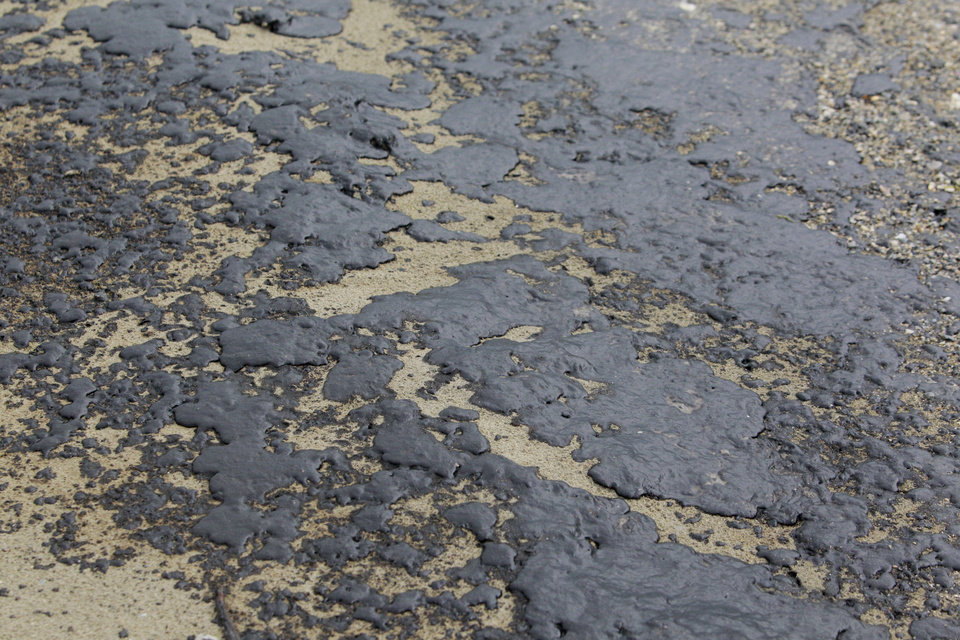 Photo - Oil is shown washed ashore on the beach area along Boddeker Rd. on the Eastern end of Galveston near the ship channel Sunday, March 23, 2014, in Galveston. (AP Photo/Houston Chronicle, Melissa Phillip)