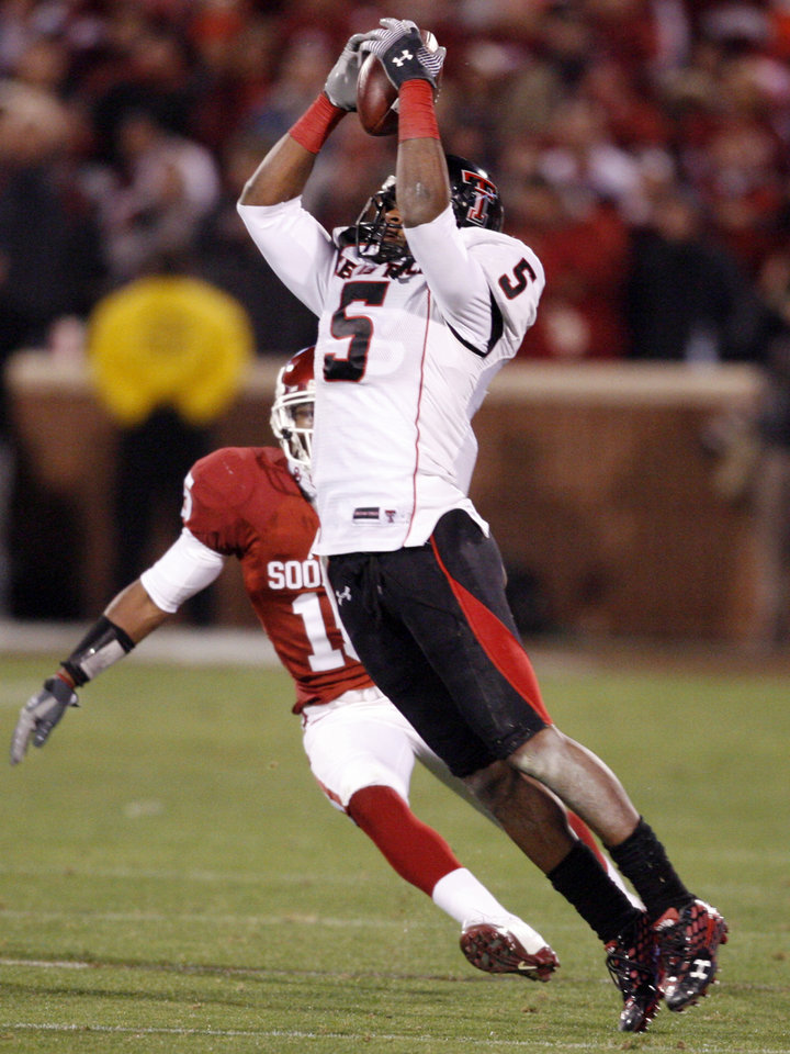 Photo - Texas Tech's Michael Crabtree (5) catches a pass during the second half and is immediately brought down by Dominique Franks (15) during the college football game between the University of Oklahoma Sooners (OU) and Texas Tech University at the Gaylord Family -- Oklahoma Memorial Stadium on Saturday, Nov. 22, 2008, in Norman, Okla.   BY STEVE SISNEY, THE OKLAHOMAN