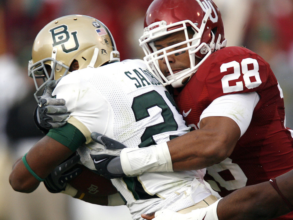 Photo - Oklahoma's Travis Lewis (28) wraps up Baylor's Jarred Salubi (21) during the second half of the college football game between the University of Oklahoma Sooners (OU) and the Baylor University Bears at Gaylord Family-Oklahoma Memorial Stadium on Saturday, Oct. 10, 2009, in Norman, Okla. 