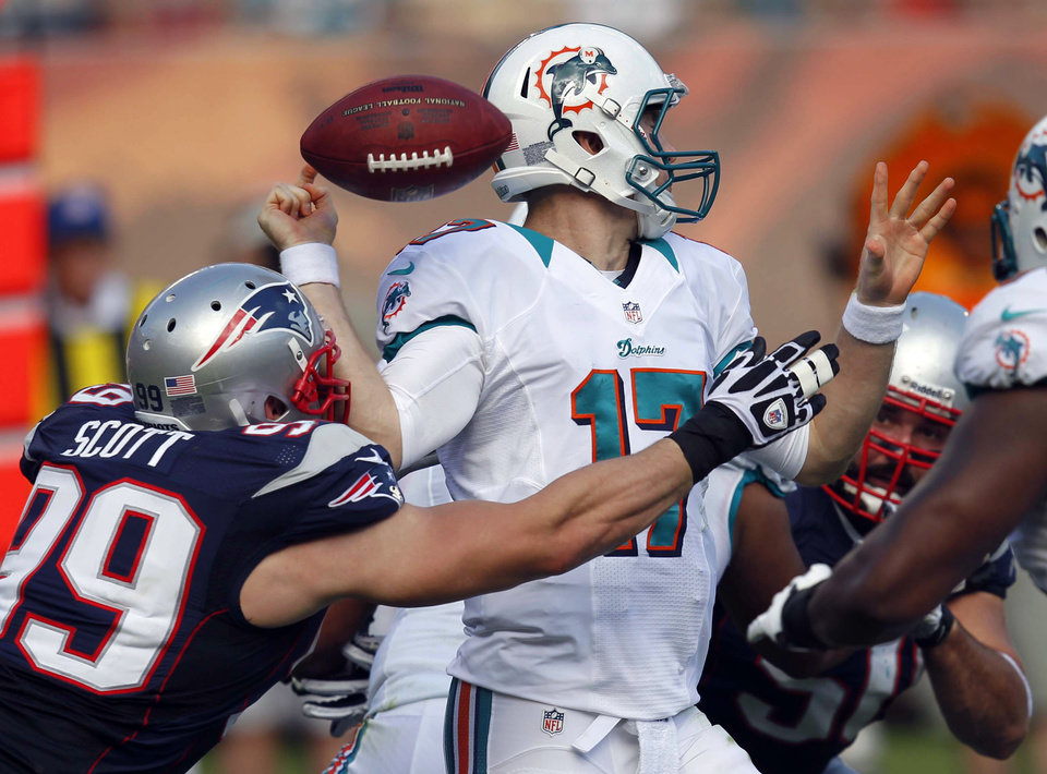 Photo - Miami Dolphins quarterback Ryan Tannehill (17) fumbles the ball after being hit by New England Patriots defensive end Trevor Scott (99) during the first half of an NFL football game, Sunday, Dec. 2, 2012 in Miami. (AP Photo/Wilfredo Lee)