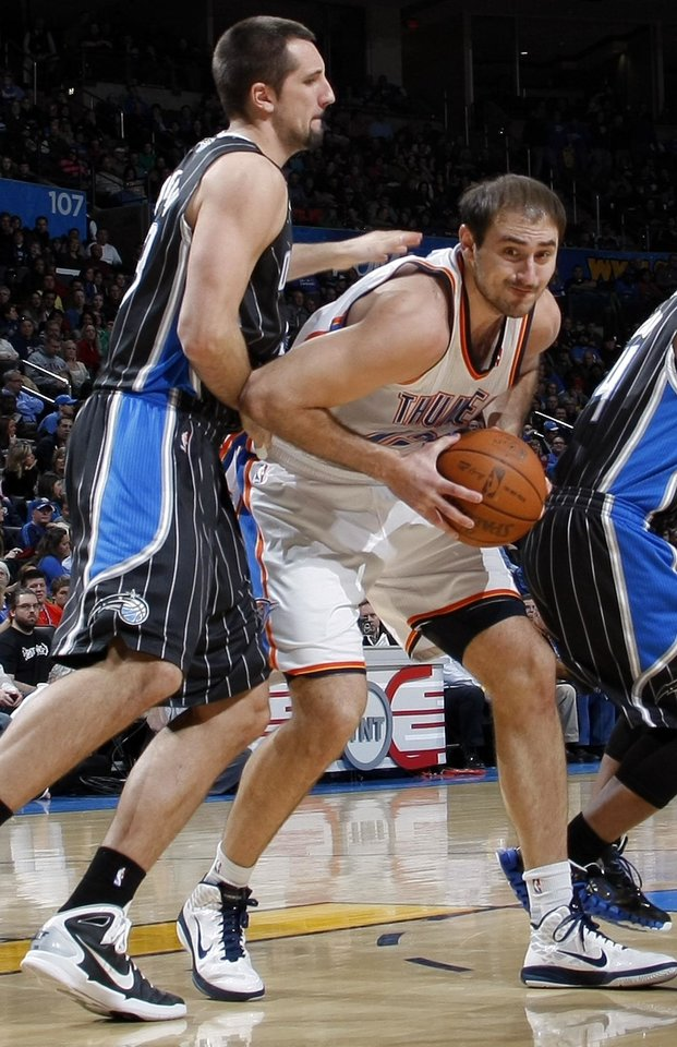 Photo -  Oklahoma City's Nenad Krstic (12) tries to get past Ryan Anderson (33) of Orlando during the NBA basketball game between the Orlando Magic and Oklahoma City Thunder in Oklahoma City, Thursday, January 13, 2011. Photo by Nate Billings, The Oklahoman