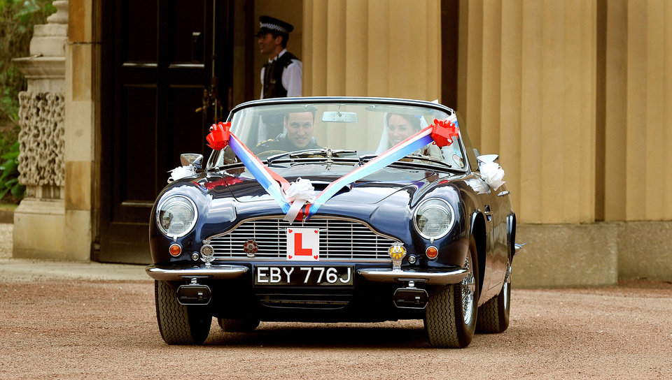 Photo - Britain's Prince William drives his wife, Kate, Duchess of Cambridge out of Buckingham Palace in London in his father Prince Charles' Aston Martin Volante sports car covered with bunting on their way to Clarence House after their wedding in nearby Westminster Abbey, in London Friday April 29, 2011. (AP Photo/John Stillwell, Pool) ORG XMIT: RWDJ145