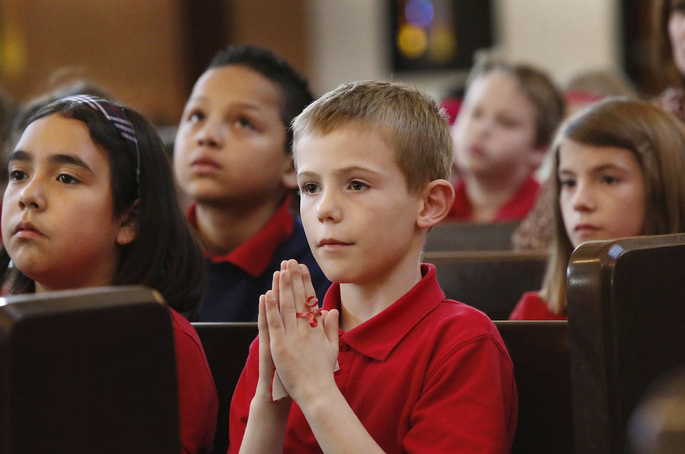 Kyle Yeakley and his fourth-grade classmates at St. James Catholic School participate in a short blessing ceremony for the school�s Jesse tree.
