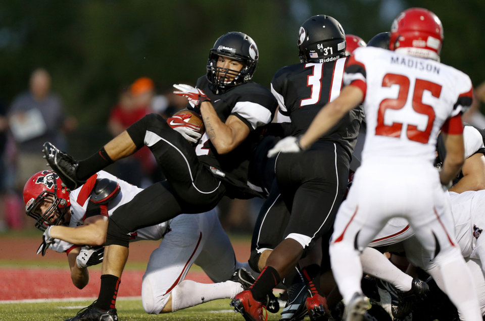 Photo - Yukon's A.J. West fights for more yards in front of Mustang's Robert Simons, left, during a high school football game in Yukon, Okla., Friday, August 31, 2012. Photo by Bryan Terry, The Oklahoman