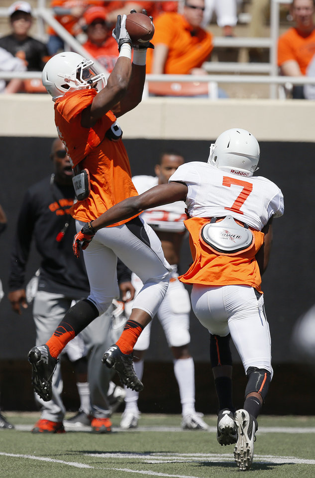 Photo - OSU's Brandon Sheperd catches a pass in front of Tre Flowers during Oklahoma State's Orange Blitz football practice at Boone Pickens Stadium in Stillwater, Okla., Saturday, April 5, 2014.