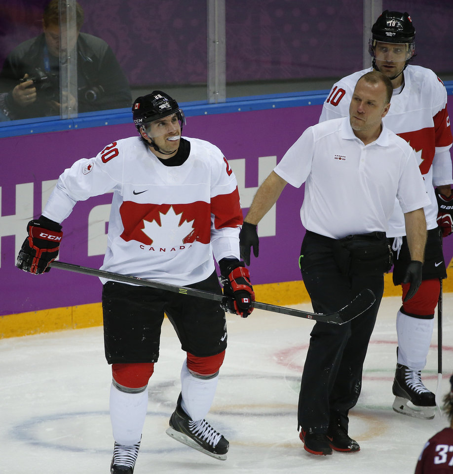 Photo - Canada forward John Tavares skates off the ice with a trainer after sustaining a leg injury during the second period of a men's quarterfinal ice hockey game against Latvia at the 2014 Winter Olympics, Wednesday, Feb. 19, 2014, in Sochi, Russia. Tavares is out for the rest of the Olympics. (AP Photo/Mark Humphrey)