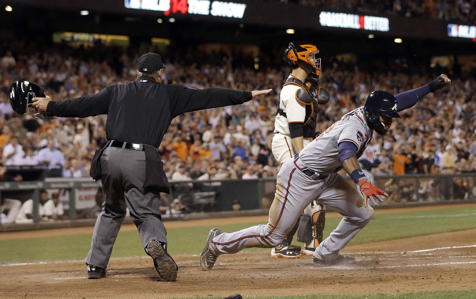 Photo - Atlanta Braves' Jason Heyward, right, celebrates after being called safe at home by umpire Ed Hickox, left, in front of San Francisco Giants catcher Buster Posey during the sixth inning of a baseball game in San Francisco, Tuesday, May 13, 2014. Giants manager Bruce Bochy challenged the ruling but the play stood. (AP Photo)