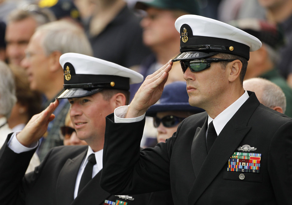 Photo -   Navy officers salute before watching their side play Notre Dame in their NCAA college football game in Dublin, Ireland, Saturday, Sept. 1, 2012. (AP Photo/Peter Morrison)