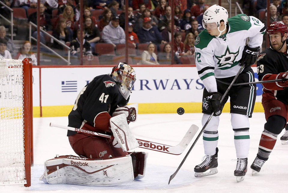 Photo - Phoenix Coyotes' Mike Smith (41) makes a save on a shot by Dallas Stars' Alex Chiasson (12) as Coyotes' Derek Morris (53) looks on during the first period of an NHL hockey game Tuesday, Feb. 4, 2014, in Glendale, Ariz. (AP Photo/Ross D. Franklin)