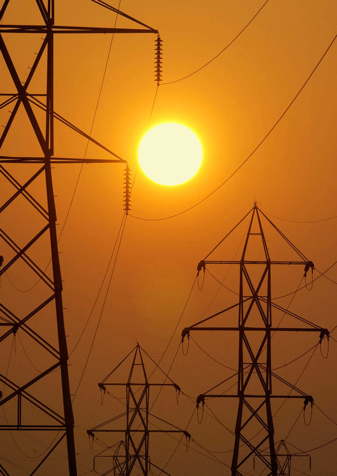 The setting sun silhouettes electric transmission lines crossing Berea, Ohio. AP Photo