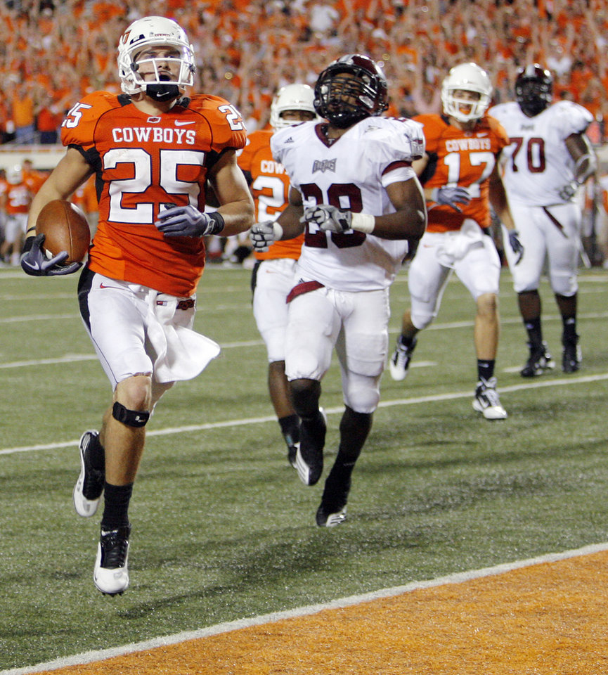 OSU\'s Josh Cooper (25) returns a punt for a touchdown in front of Troy\'s Cameron Hudson (28) in the third quarter during the college football game between the Oklahoma State University Cowboys (OSU) and the Troy University Trojans at Boone Pickens Stadium in Stillwater, Okla., Saturday, Sept. 11, 2010. OSU won, 41-38. Photo by Nate Billings, The Oklahoman