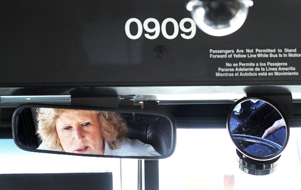 Photo - Linda Robinson, 55, seen in the rearview mirror of a Metro Transit bus, has been driving buses for 34 years.  Photo by Jim Beckel, The Oklahoman