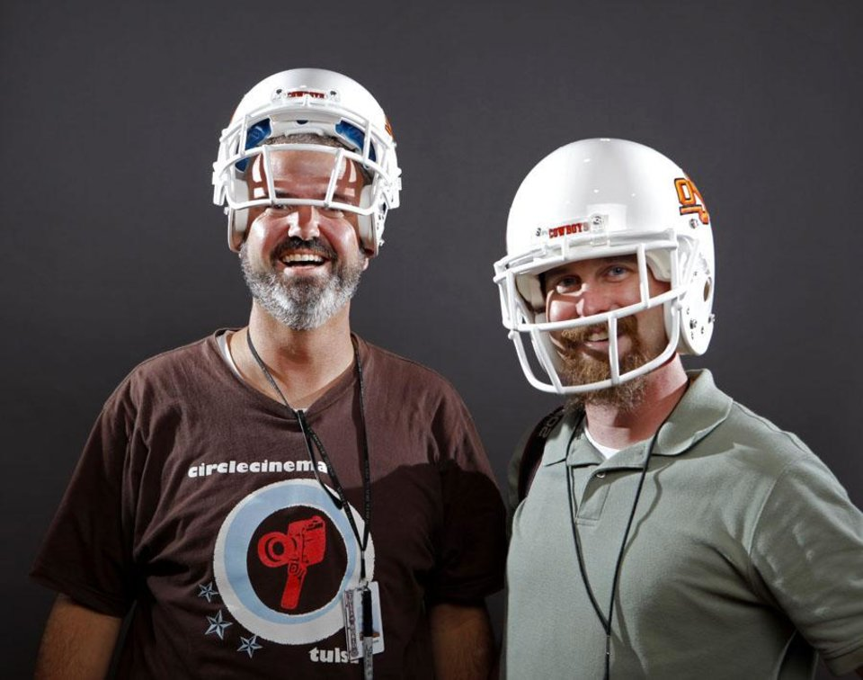 Tulsa World Photographer Mike Simons (left) and The Oklahoman photographer pose with OSU helmets that fit to varying degrees. Photo by Bryan Terry, The Oklahoman