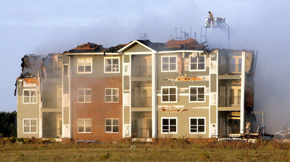 A fireman directs water onto hot spots during a fire at an apartment complex under construction near Covell Road and Kelly Avenue in Edmond Tuesday, Oct. 20, 2009. Photo by Paul B. Southerland, The Oklahoman