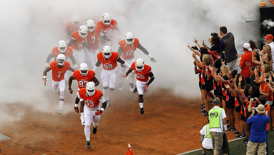 Photo - The OSU Cowboys take the field before a college football game between the Oklahoma State University Cowboys (OSU) and the Lamar University Cardinals at Boone Pickens Stadium in Stillwater, Okla., Saturday, Sept. 14, 2013. Photo by Nate Billings, The Oklahoman