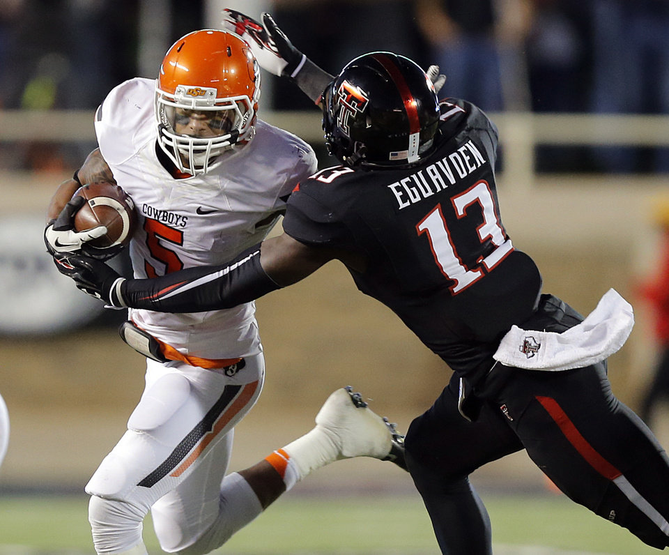 Oklahoma State 's Josh Stewart (5) runs past Texas Tech's Sam Eguavoen (13) during the college football game between the Oklahoma State University Cowboys (OSU) and the Texas Tech University Red Raiders (TTU) at Jones AT&T Stadium in Lubbock, Tex. on Saturday, Nov. 2, 2013.  Photo by Chris Landsberger, The Oklahoman